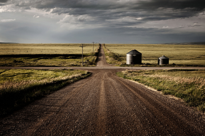 Intersecting dirt roads in Idaho, with fields and silos on the side of the road.