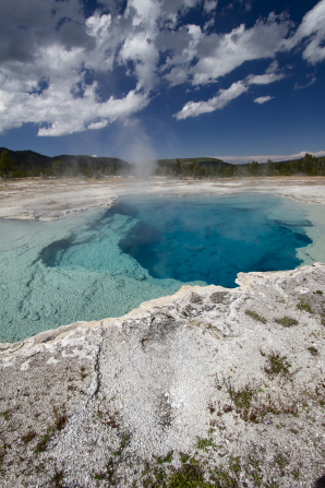 Hot springs by a hillside at Yellowstone National Park, with clouds in the clear, blue sky.