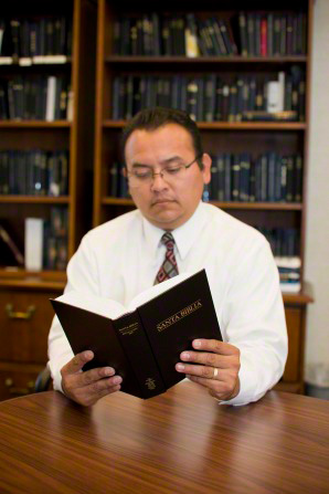 A man in a white shirt and tie sits at a table and reads a Spanish Bible, with several shelves of books seen in the background.