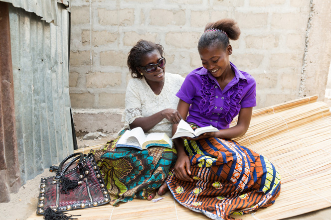 A mother sits next to her daughter on a mat, and they hold their scriptures open on their laps.