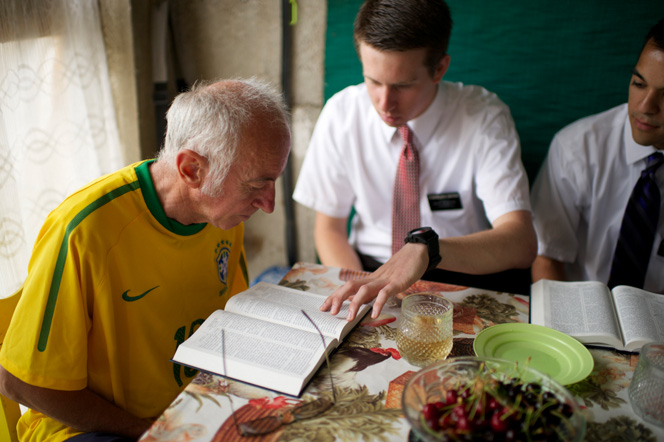 A man in a yellow jersey reads the scriptures along with two elders at his dinner table.