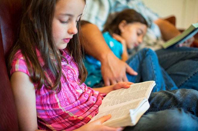 A young girl reads from her scriptures while her father and sister sit next to her on the couch.