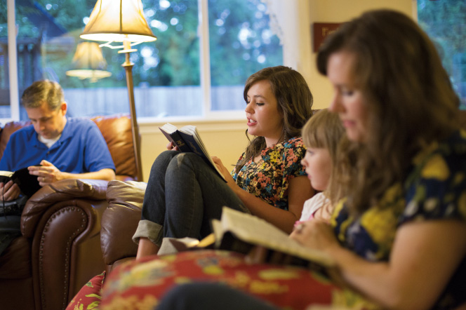 A young woman reads from the scriptures while her mother, father, and sister sit in the living room with her and follow along.