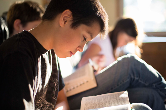 A young boy leans over his scriptures and reads along with his family in their living room.