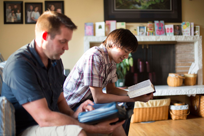 A young man reads his scriptures while his father sits next to him on the couch and follows along with him.