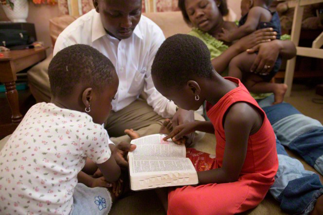 A father sits on the ground next to his two daughters and wife and helps his daughters read from the scriptures.