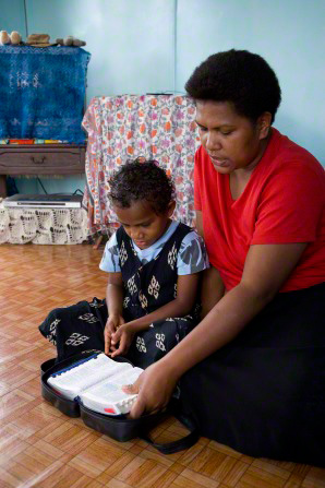 A mother sits on the floor next to her young daughter and reads from the scriptures as her daughter listens.