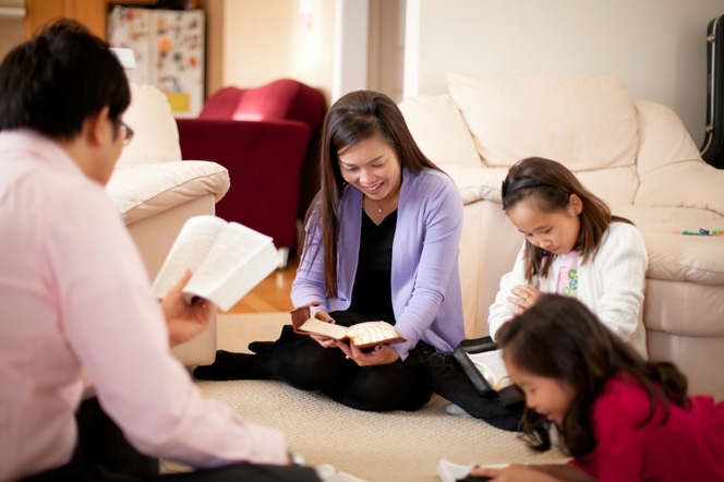 A mother and father sit on the carpet with their two daughters and read scriptures together.
