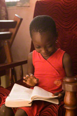 A little girl in a pink dress sits in a red chair and flips the pages of a set of scriptures.