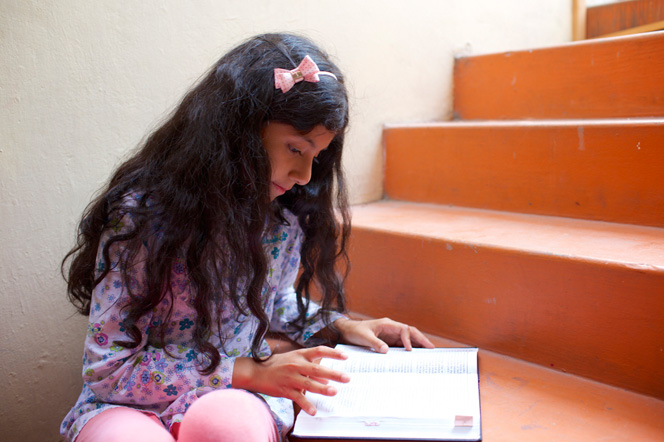 A young girl with a bow in her hair sits on the steps and reads from her scriptures.