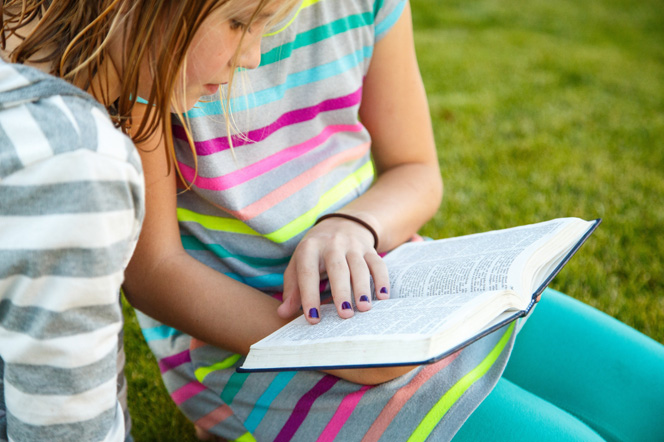 Two young girls in striped shirts sit on the grass and read the Book of Mormon together.