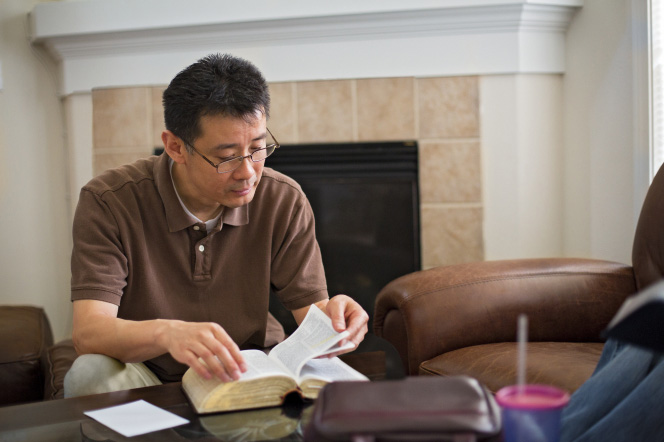A man sits on a chair in his living room and flips the pages of a set of scriptures on the table in front of him.