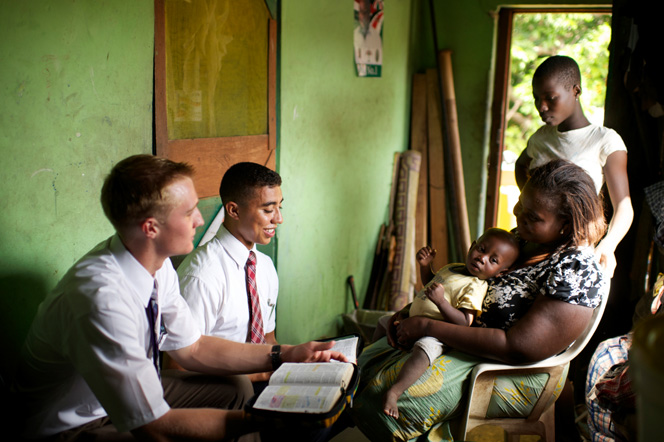Two missionaries read scriptures to a woman who has a child in her lap and another child standing next to her.