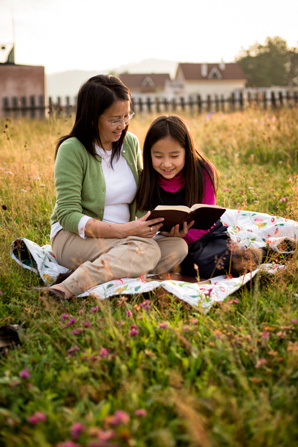A mother sits next to her daughter on a blanket in a field and holds a set of scriptures open while her daughter reads from them.