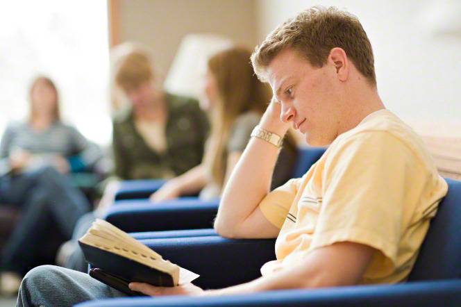 A young man sits in a chair and rests his head on his hand as he reads from the scriptures, with other young adults in the background.