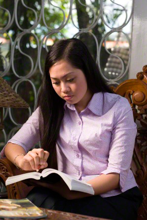 A young woman with long dark hair, sitting in a chair, reading and marking the scriptures that she holds in her hand.