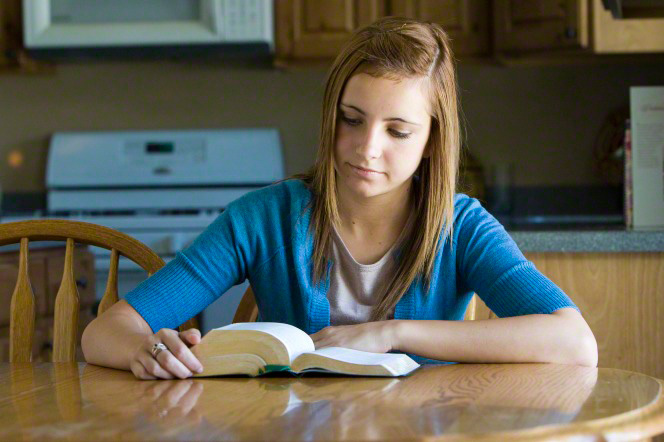 A young woman in a blue sweater sits at a table in the kitchen and reads her scriptures, which are on the table.