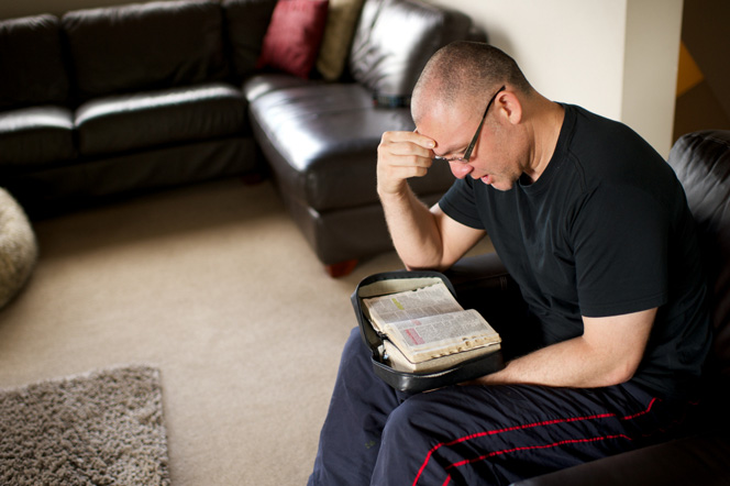 A man sits in an armchair with his scriptures in his lap and reads from them.