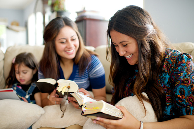 Two young women sit side by side on a couch and read from their scriptures with a little girl sitting next to them.