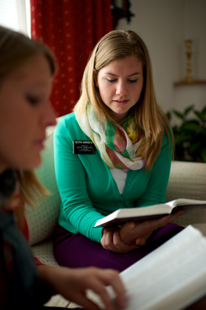 Two sister missionaries sit side by side on a couch, each reading the scriptures.