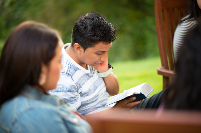 A young man sits outside and reads from the scriptures while a group of young adults sit nearby and listen.