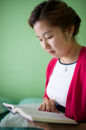 A young woman in a pink sweater sits on her bed next to a pale green wall and reads from her scriptures.