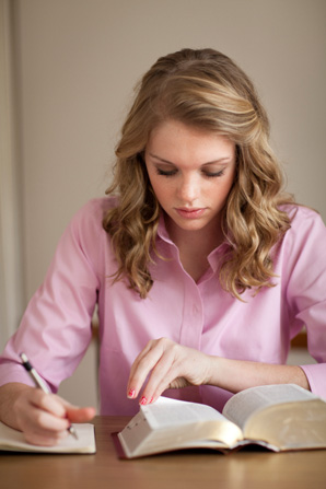 A young woman sits at a table and writes in a study journal while reading from a set of scriptures.