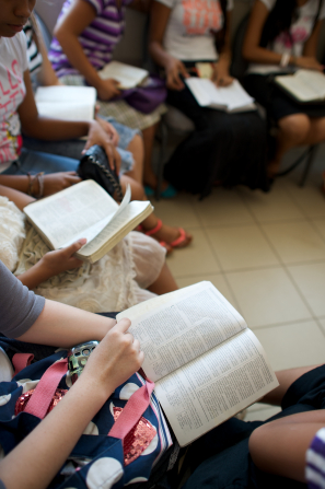 A group of youth sitting in a circle at church while reading from scriptures held open in their hands.