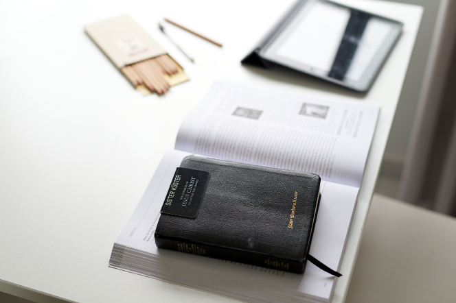A sister missionary's badge lying on top of her hardbound scriptures and an open book.