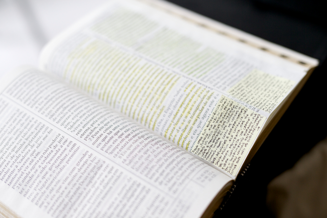 Hardbound Portuguese scriptures with yellow highlights and sticky notes.