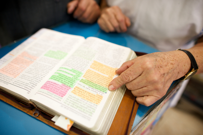 A woman pointing at a green-highlighted verse in a well-marked set of scriptures.