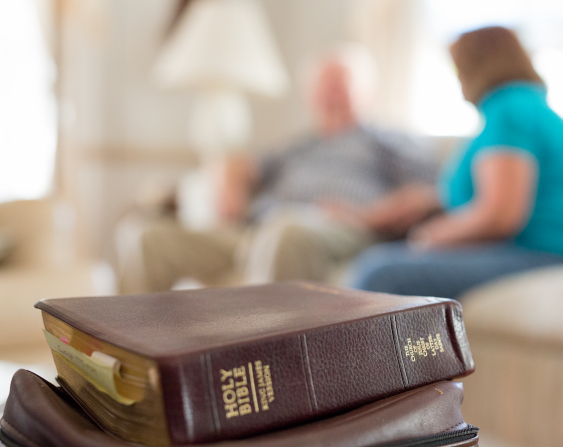 A Bible on top of a scripture case on a table, with a man and woman sitting on a couch in the background.