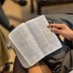 A young man reading the Book of Mormon during a youth study group.