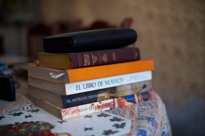 A stack of Spanish books, including scriptures and other study materials, lying on a tablecloth.
