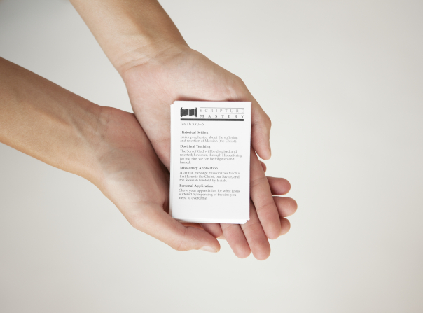 Two hands holding a stack of white scripture mastery cards with Isaiah 53:3–5 on the top.
