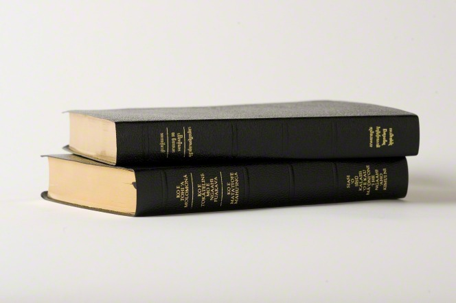 Two triple combinations in black leather printed with gold ink, lying in a stack.