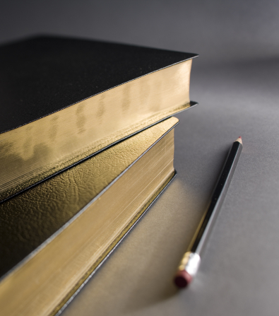 A set of black leather-bound scriptures lying next to a red marking pencil on a gray surface.