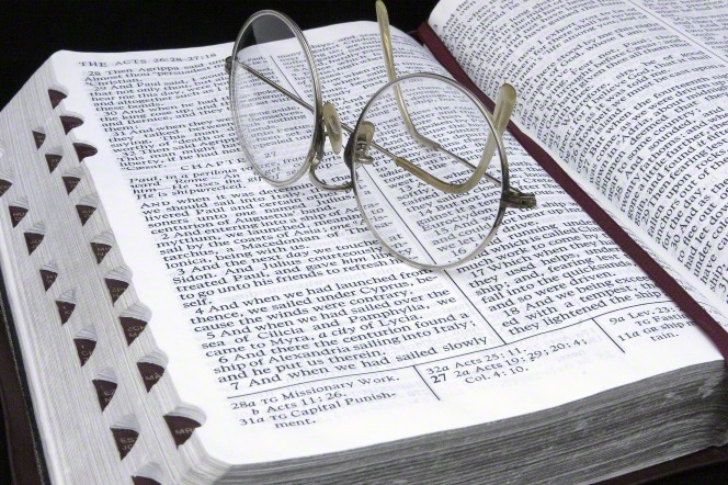 A pair of rounded wire-frame eyeglasses lying on top of a Bible, which is opened to Acts chapter 27 and marked with a maroon ribbon.
