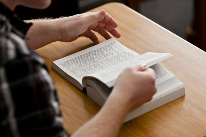 A man's hands flipping through the pages of a paperback Bible in front of him on a desk.