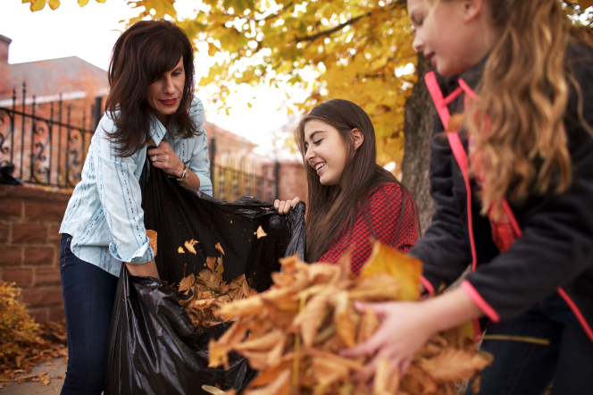 A mother and her two daughters work together to clean up fallen leaves and put them in a garbage bag.