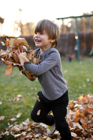 A young boy is playing outside, running with a pile of leaves in his hands and a smile on his face.