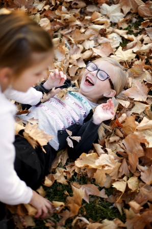 A young girl, out of focus, is outside on an autumn day, piling leaves on her younger sister, who is in focus.