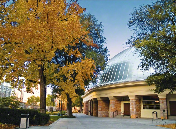 Part of the exterior of the Salt Lake Tabernacle on Temple Square in Utah, with surrounding trees changing from green to yellow in the fall.