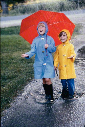 A girl in a blue raincoat holds a red umbrella and plays in the rain with a girl in a yellow raincoat.