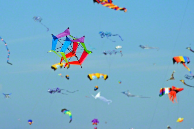 A group of colorful kites against a clear blue sky.