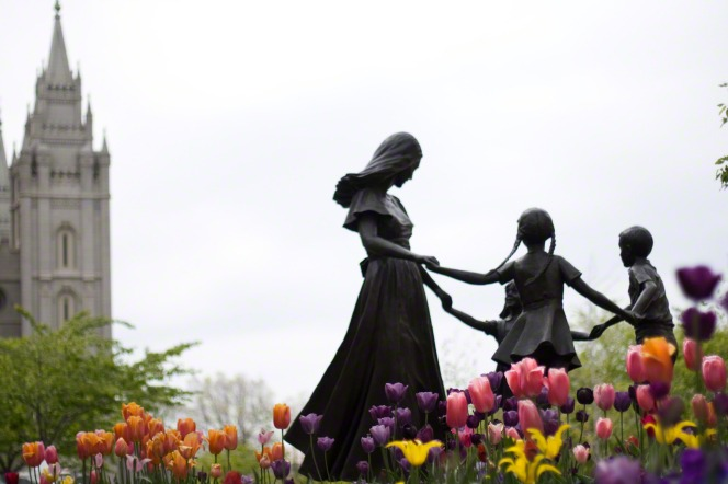 A sculpture of a family on Temple Square has colorful tulips blooming around it, with a view of the Salt Lake Temple in the background.