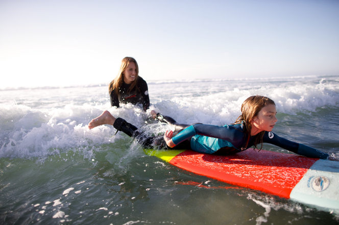 A mother sits on her surfboard in the water and watches her daughter paddle out in front of her on her surfboard.