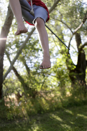 A child's feet dangle below a rope swing outside.