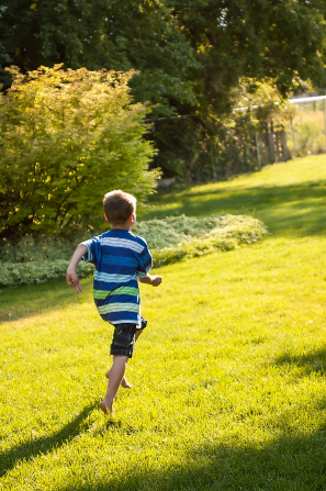 A little boy in a striped shirt and shorts runs on the grass with his back to the camera.