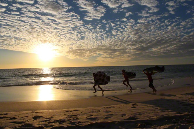 Silhouettes of three children carrying towels in the wind and running along the beach, with the sun starting to set behind them.